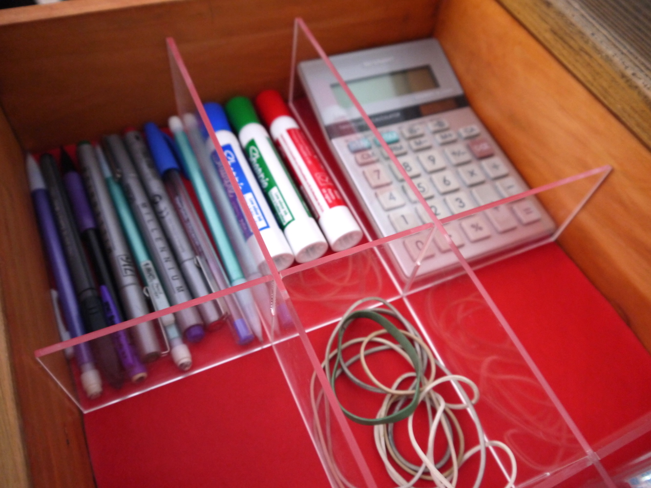 acrylic grid organizer on red mat in desk drawer